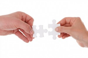 hands holding two jigsaw pieces
