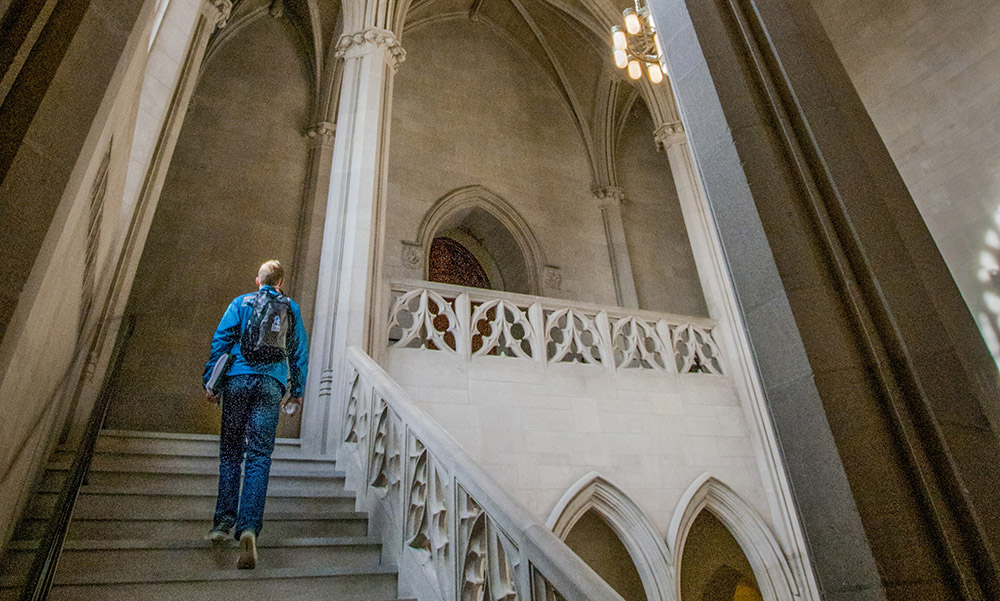 student ascending gothic stairway